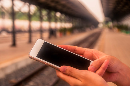 hand of human using smartphone with blurred straight railway back ground at station.