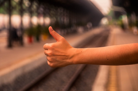 hand of human showing thumb up with blurred straight railway back ground at station.