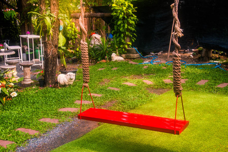 Red wooden swinging on park with green grass.relaxing concept.