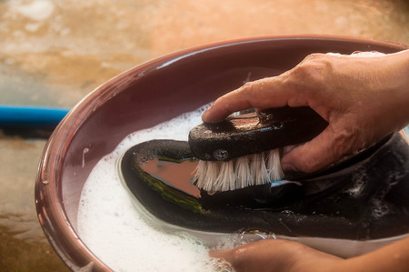 Woman hand cleaning black shoes or sneaker by wooden brush and soapsuds on bowl