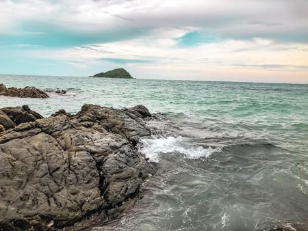 Sea waves splashing with stone reef off the coast and blue sky. Sea foam breaking on coastal rock