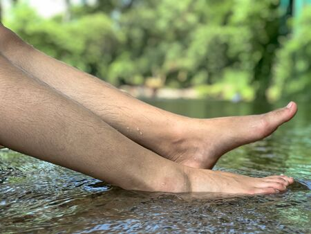 Woman leg in the water at waterfall,relax time with nature