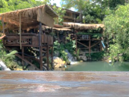 Empty wood table with blurred river and wooden house