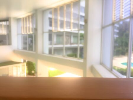 Empty wooden railing with blurred window and light