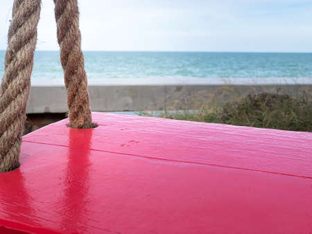 Close up of empty red swing sit with sea background.