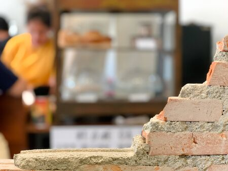 Empty bricks wall with blurred cafe background.