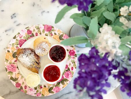 scones with jam and cream, tea break time with dessert on marble table