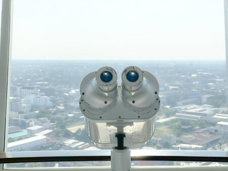 binoculars for tourist inside the building and city background.