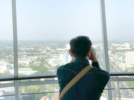 Asian tourist watching the city by binoculars inside the building