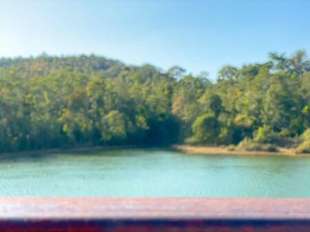 Blurred wooden bar with river and forest background.