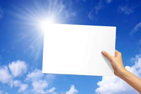 nature photo: white paper in woman hand on blue sky background.