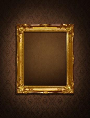 antique gold frame: Gold frame stuck on the wall wallpaper thai the dark.  Stock Photo