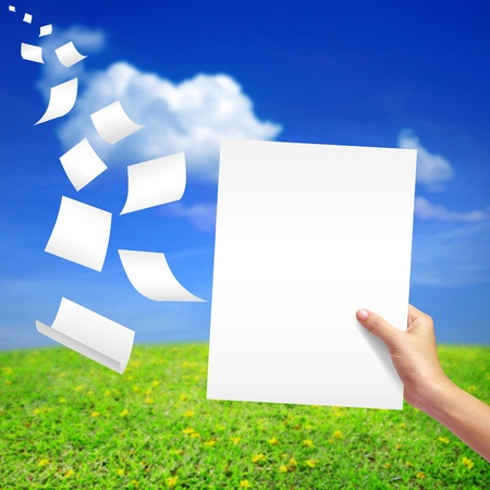 white paper in hand on natural background.  photo