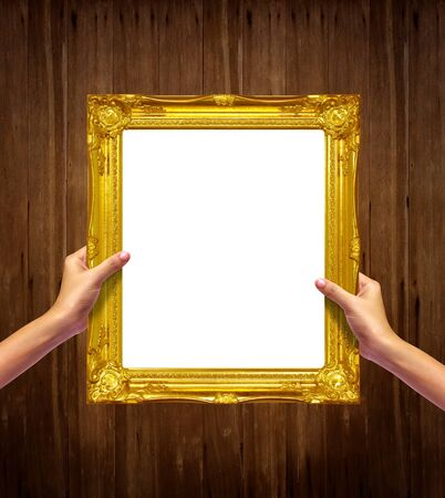 gold frame in woman hand isolated on old wood background  photo