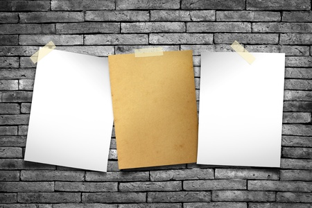 tile adhesive: White paper and old paper. Stick tape on the gray brick wall Stock Photo