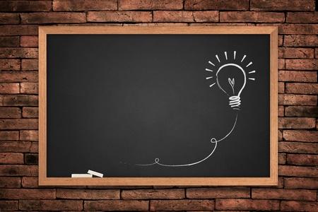 educadores: Dibujo de una pizarra de idea de bombilla sobre fondo de pared  Foto de archivo