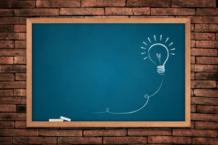 Drawing of a bulb idea blue board on wall background  photo