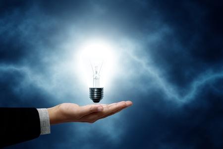 bolts: Light bulb hanging on business men. The background is a blue lightning bolt