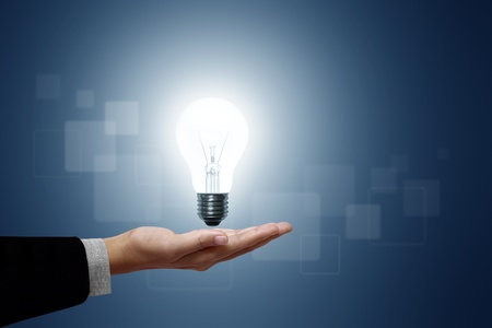 electric bulb: Light bulb in hand businessman on blue background.  Stock Photo