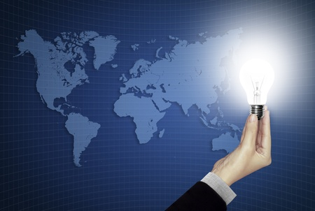 Bulb light in hand on world map blue background  photo