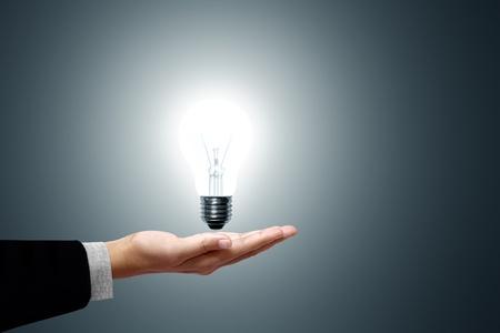 Birnen-Licht in der Hand auf grauem Hintergrund