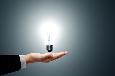 save electricity: Bulb light in hand on gray background Stock Photo