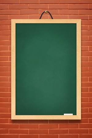 blackboard cartoon: green board hanging on a brick wall. Stock Photo