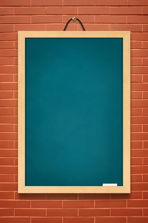 wooden frame: blue board hanging on a brick wall. Stock Photo