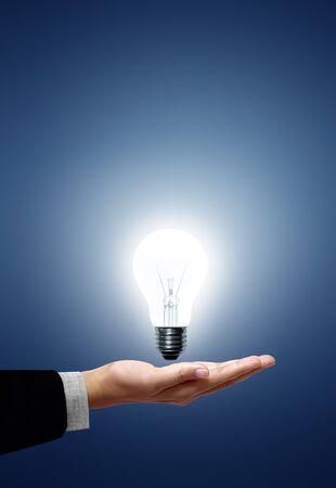 electric bulb: Light bulb in hand businessman on blue background Stock Photo