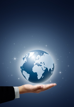 holding a glowing earth globe in his hands on blue background photo