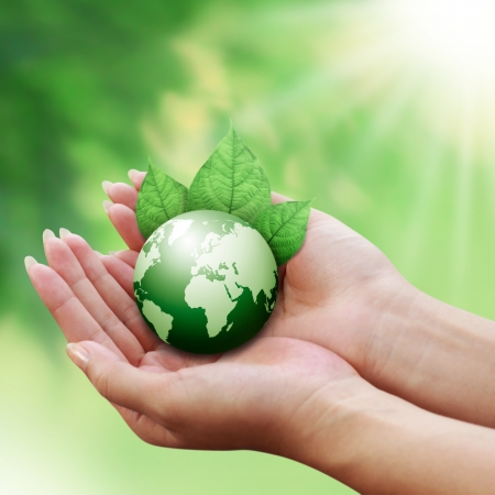 green planet: human hands holding green earth with a leaf  Stock Photo