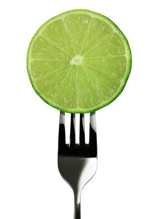 lemon juice: lemon green on fork isolated on white background