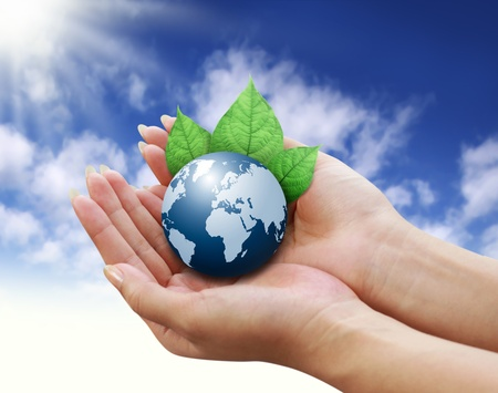 human hands holding blue earth with a leaf on sky background  Stock Photo - 11169551