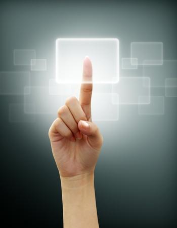 mano touch: mano premendo un pulsante su una interfaccia touch screen su sfondo grigio