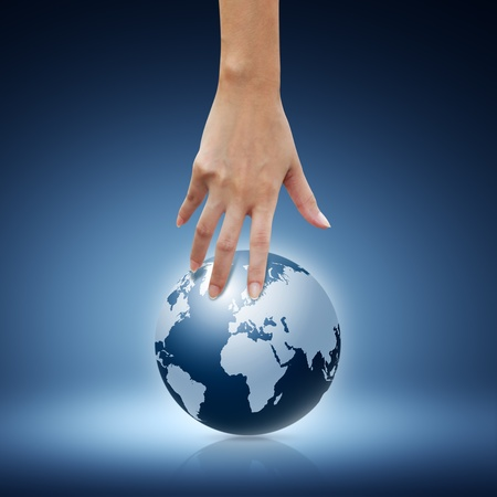 Women hand pointing down to the globe on blue background photo