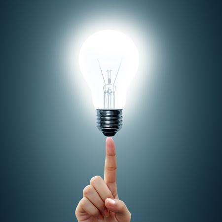 fingertip: bulb light on women Fingertip on blue background  Stock Photo