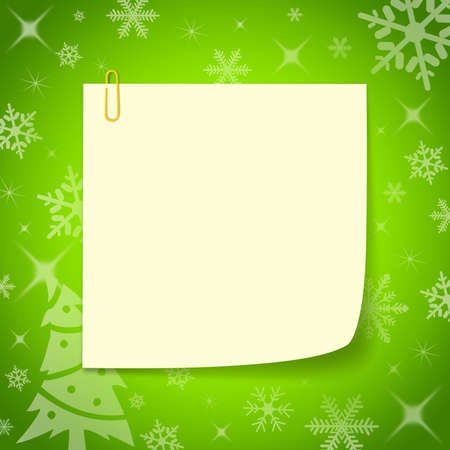 wish list: Cream colored paper notes. with clip placed on the surface of a green Christmas.