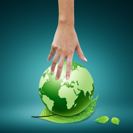 Women hand pointing down to the green globe and leaf photo