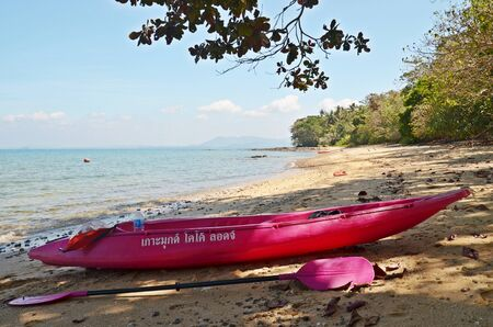 cayak: lonely beach landscape with purple canoe boat on ko mook island in thailand Stock Photo