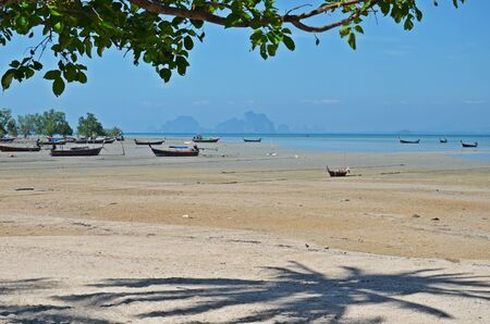 mook: low tide and boats on shore in ko mook island, thailand