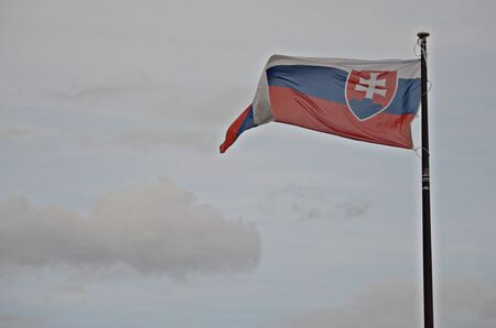slovak: slovak national flag blowing in the wind, grey clouds on the background