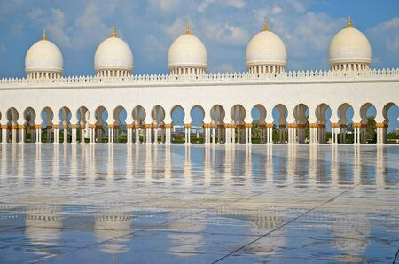 sheik: White pillars and their reflection on marble floor in Sheik Zayed Grand Mosque in Abu Dhabi in United Arab Emirates.