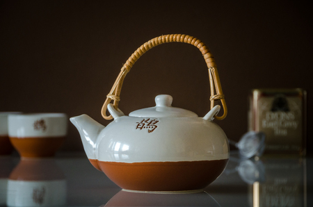 Japanese tea pot with cup, strainer and box of earl grey tea in the background.