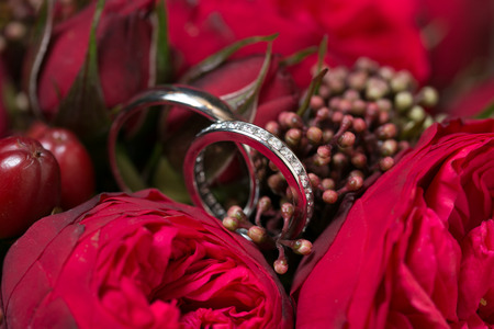 Wedding rings and red roses bouquet photo