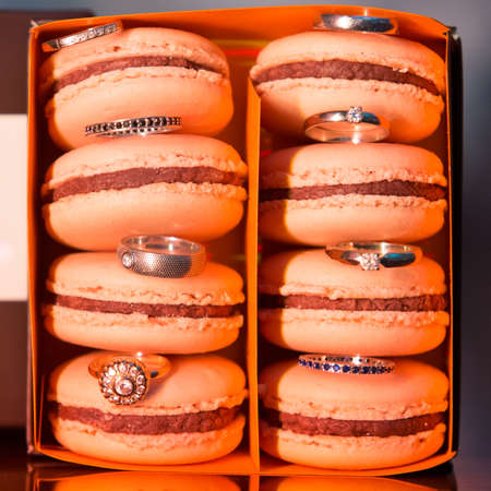 Colorful and tasty orange Macaroons in paper box with wedding rings photo