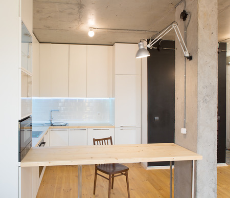 Modern and stylish white kitchen. Concrete ceiling. Wooden floor and countertop photo