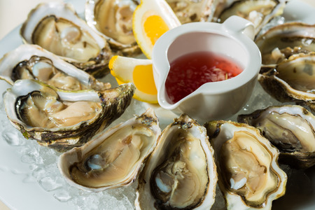 A platter of fresh organic raw oysters on ice at restaurant Archivio Fotografico