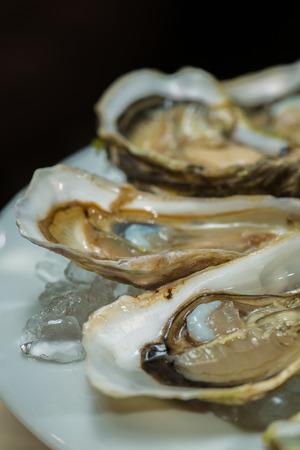 Eine Platte mit frischen Bio-rohe Austern auf Eis im Restaurant