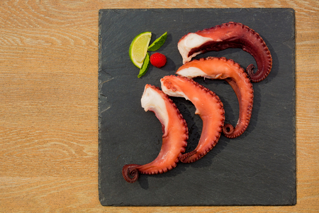 Cooked Octopus Plate with lime in black stone background. Close up photo