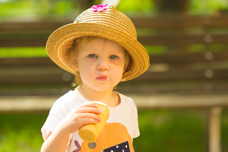 Cute Toddler Girl Eating Ice-Cream at park at background photo
